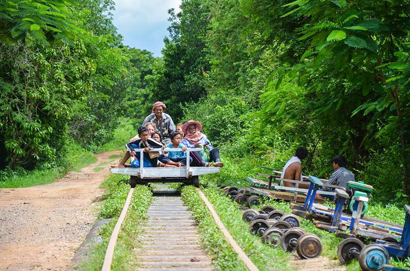 Пассажиры едут по железнодорожным путям на бамбуковой платформе размером примерно с двуспальную кровать, на которой установлены две пары металлических колес, приводимых в движение двигателем.